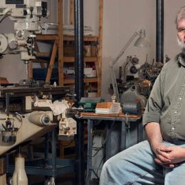 Jonathan Larrabee, the face of HMH Fly Tying Vises, sits with a newly finished vise in his shop at the Pepperell Mill Campus, photographed by Portland Headshot.